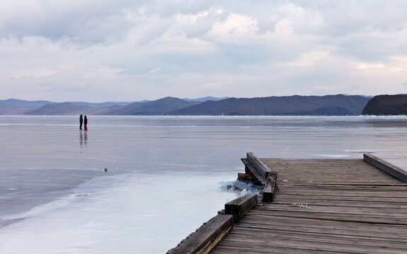 Baikal Lake on a cold December day. Frozen wooden pier on the Kurkuta Bay. Tourists walk on ice and skate during winter holidays