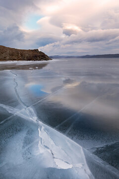 Unusual winter landscape with the reflection of pink clouds on the blue smooth surface of the ice on the frozen Lake Baikal at sunset. Natural ice texture, cold blue background, close-up view