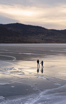 Top view of the silhouettes of a young couple of tourists ice skating on the ice of the frozen Baikal lake at sunset. Happy winter holidays, active fun pastime