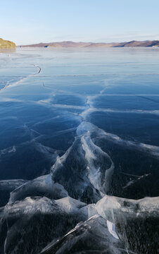 Close-up view of cracks in the blue smooth surface of the ice on frozen Lake Baikal at sunny frosty day. Unusual winter landscape. Natural ice texture, cold blue background