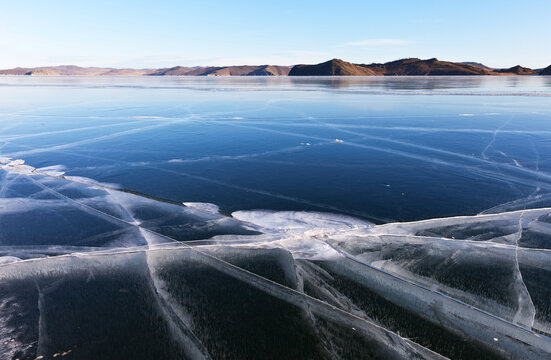Unusual winter landscape with a cracks in the blue smooth surface of the ice on frozen Lake Baikal at sunny frosty day. Natural winter background