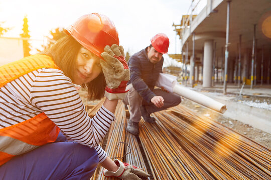 Woman as a worker on construction site for house building with material