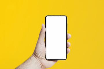 Iphone trzymany w ręce na kolorowym tle. Pusty ekran do wypełnienia