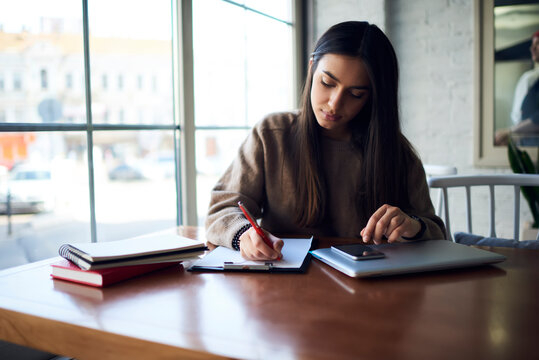 South Asian female student with closed laptop and cellphone writing education information on white A4 pages during time for e learning in coworking space, millennial woman making notes at desktop
