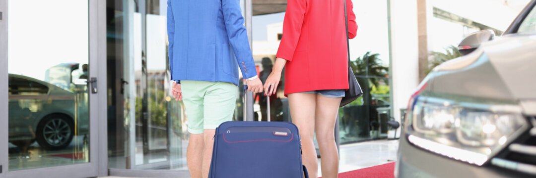 Man and woman with suitcase get out of taxi to airport building