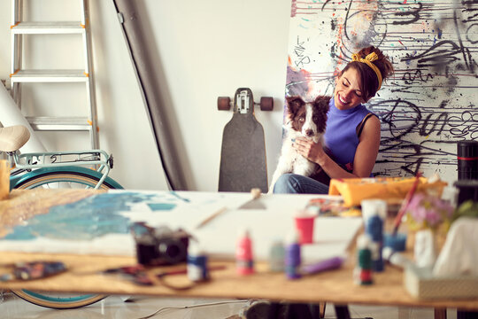 A young female artist is enjoying a break with her dog while working on a new painting in the studio. Art, painting, friendship, studio