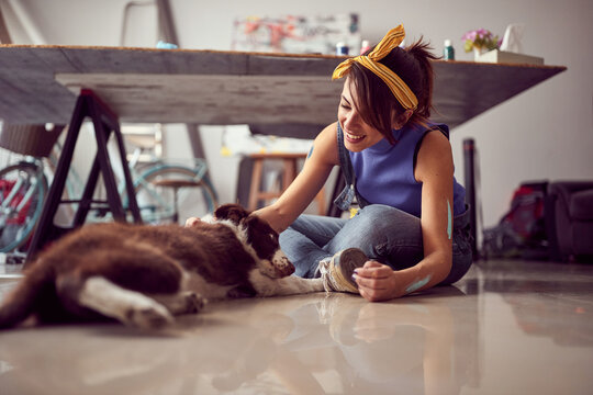 A young female artist is sitting on the floor in the studio and playing with her dog while making a break from work on a new painting. Art, painting, friendship, studio