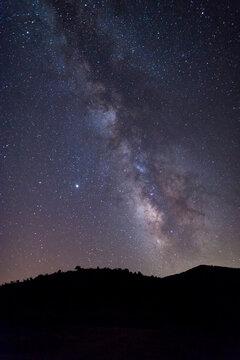 Milky Way starry night sky over hills and trees Sardinia Italy