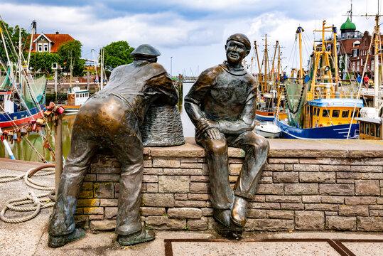 Neuharlingersiel, East Frisia, Germany, 07-04-2021:Neuharlingersiel with bronze monument of two fishermen created by the Petersen brothers