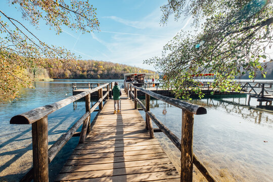 Croatia nature park Plitvice Lakes in autumn. Boy walking on wooden pier on the lake before ferry departure.