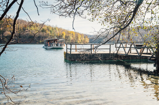 Croatia nature park Plitvice Lakes in autumn soft colors. A ferry full of people departed from the wooden pier on the lake.