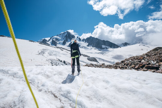 Young female Back view portrait Rope team member on acclimatization day dressed mountaineering clothes walking by snowy slopes in climbing harness and green dynamic rope on the close-up foreground.