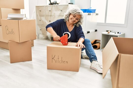 Middle age grey-haired woman smiling happy packing kitchen cardboard box at new home.