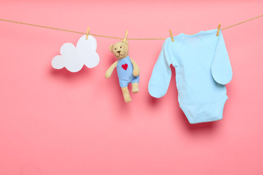 Baby clothes on a clothesline on pink background .