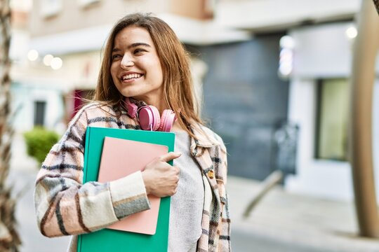 Young blonde woman wearing headphones smiling confident holding books at street