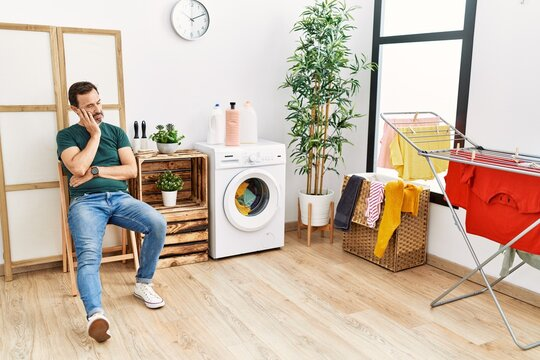 Middle age hispanic man doing laundry waiting at home.