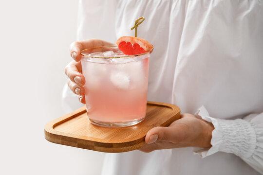 Woman holding glass of tasty grapefruit margarita on light background, closeup