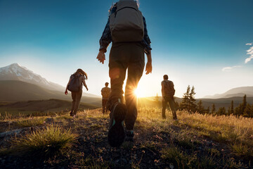 Group of sporty people walks in mountains at sunset with backpacks. Altai mountains, Siberia, Russia.