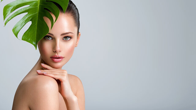 Beautiful woman with green leave near face and body.  Closeup girl's face with green leave. Skin care beauty treatments concept.