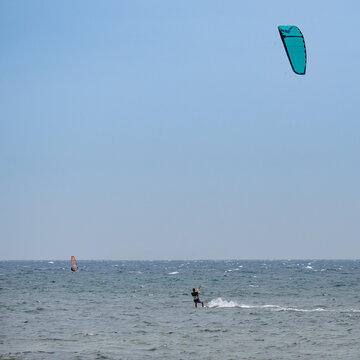 Kitesurfing and Windsurfing During a Windy Day with a Very Rough Sea