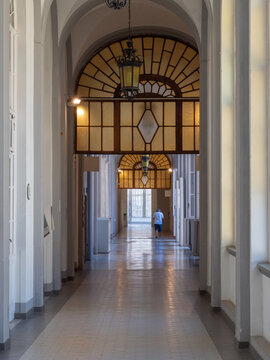 Long interior Corridor of a Hospital with Large Windows and People Walking Around.
