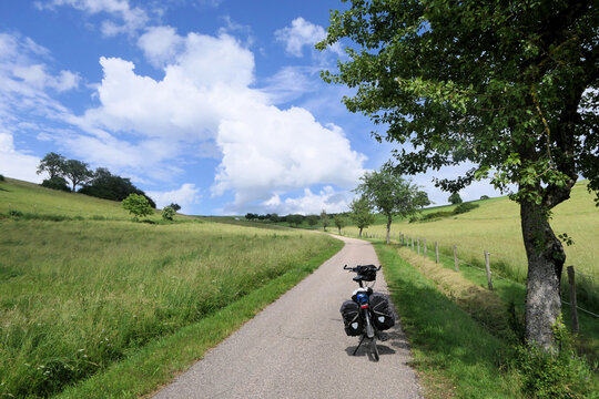 Summer feeling, a bike with panniers stands in the midday sun on a lonely road between two hilly meadows.