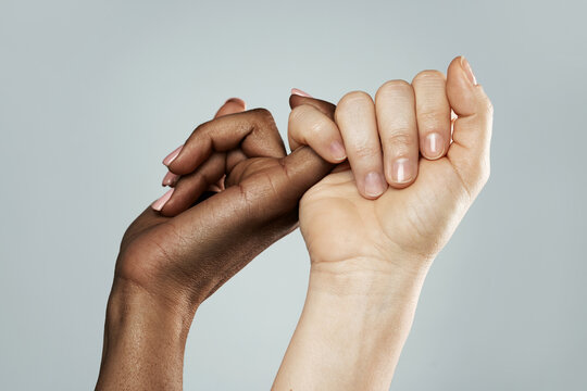 A pinky promise gesture between African and Caucasian women. Closeup of palms on gray background.
