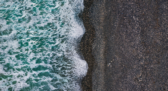 Dramatic stormy waves with white sea foam over black sand beach, aerial sea texture