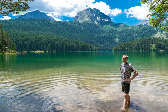 Man tourist near glacial Black Lake with Meded Peak. Tourist attraction of Durmitor National Park.