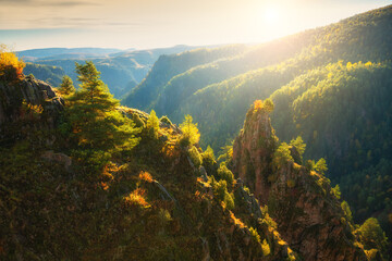 Mountains and rocks with green and yellow autumn trees at sunrise. Gil-Su valley in North Caucasus, Russia. Beautiful autumn landscape