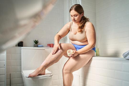 Woman applying scrub on leg while scrubbing