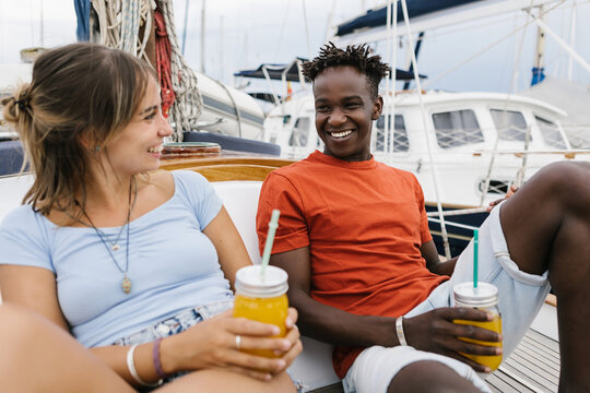 Multiracial friends cheering and laughing outdoors - Black man and hispanic woman toasting orange juice on a boat while hanging out - Friendship, youth and millennial people concept