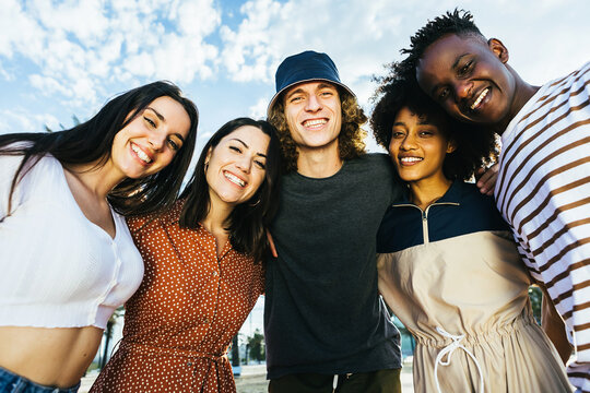 Portrait group of young happy multiracial people standing outdoors in a sunny day - Cheerful multicultural friends embracing in the street - Community and unity concept