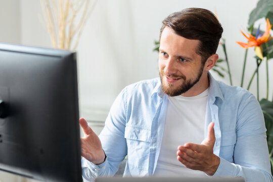 Successful young businessman in a modern office participates in an online conference with colleagues or partners, video call, handsome caucasian man working from home