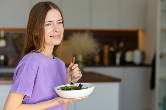 Young and happy caucasian woman eating healthy salad standing in the home kitchen, healthy lifestyle
