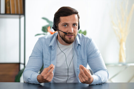 Young adult man call center worker or manager in headset looking at the webcam, having online business meeting. Head shot portrait of successful employee communicates with colleagues via video call