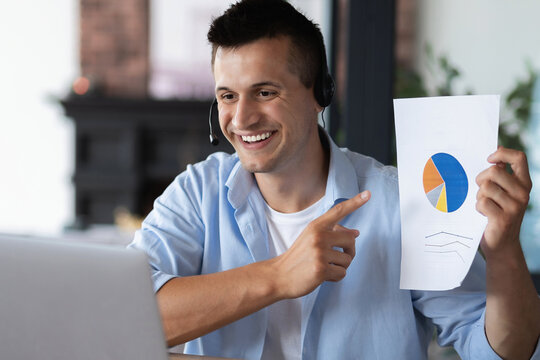 Smiling confident businessman, teacher and coach, shows the financial schedule to his employees in a webcam laptop computer, sitting at a table in the office or at home