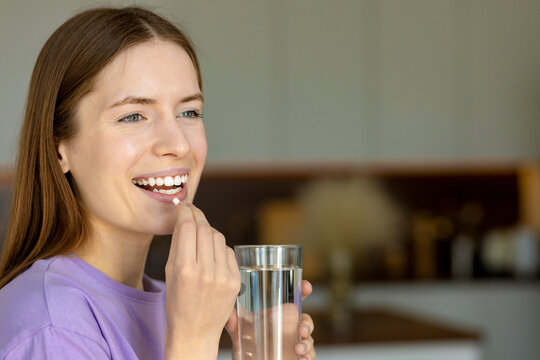 Smiling young woman puts food supplement capsule or antibiotic antidepressant in her mouth. Copy space