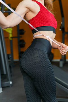Close up of slim woman measuring her waists size with tape measure.