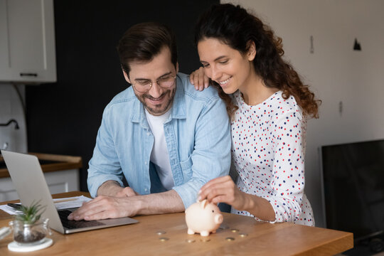 Young married couple in domestic kitchen with laptop put coins in piggy bank, spouses saving money, planning family budget, making investment in future, down payment on first affordable house concept