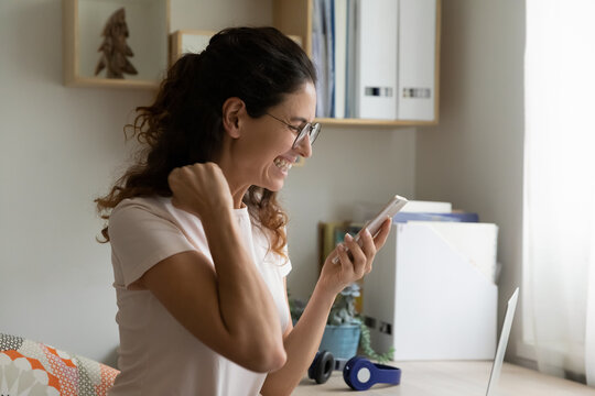 Overjoyed millennial 35s woman sit at desk holding smartphone feels euphoric reading good sms news, get amazing sale offer low price discount, online lottery victory winner celebrate success concept