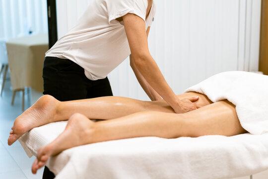 Middle-aged woman having a leg massage in a beauty salon.