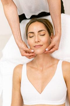 Middle-aged woman having a head massage in a beauty salon.
