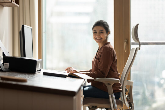 Modern day worker. Portrait of happy biracial business woman freelancer sit by computer at comfy workplace at corporate workspace or at home. Smiling young indian lady office employee look at camera
