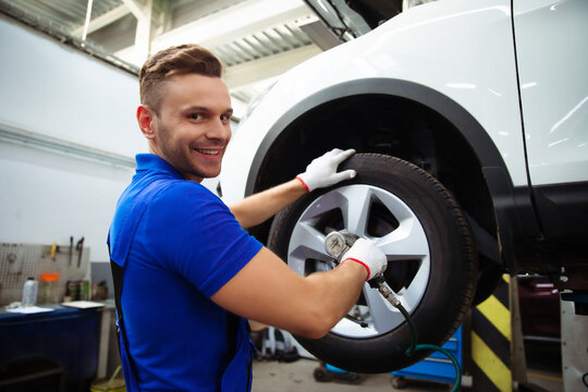 Handsome professional car mechanic changes a wheel on a car or carries out a tire change at a specialized auto repair center