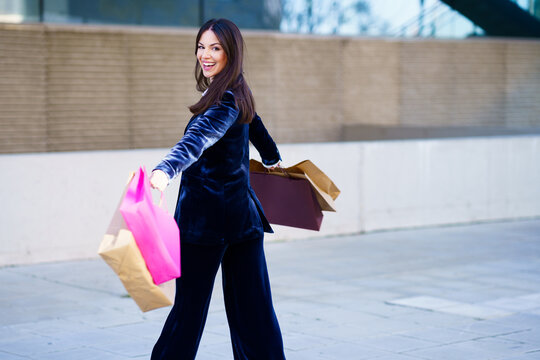 Happy woman turning with joy for her purchases in shopping bags.