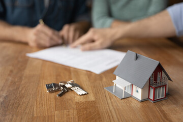Obraz Crop close up of keys and small house carton mock-up model on table in real estate agent office. Couple buyer sign document make deal close agreement in background, buy home together. Rent concept. - fototapety do salonu