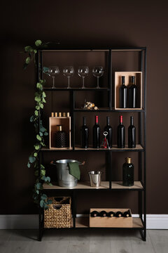 Rack with bottles of wine and glasses near brown wall