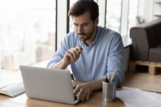 Pensive serious young Caucasian man sit at desk in office look at laptop thinking pondering. Thoughtful male employee work online on computer make plan or decision, brainstorm at workplace.
