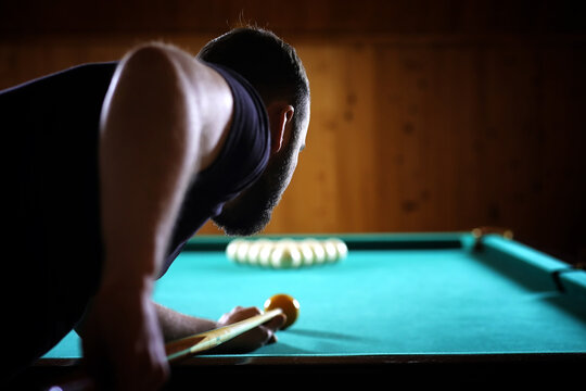 A man with a beard plays a big billiard. Party in a 12-foot pool. Billiards in the club game for men. A man with a cue breaks the pyramid.